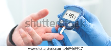 Doctor making blood sugar test in clinic. Blood sugar measurement in a medical clinic #1469469917