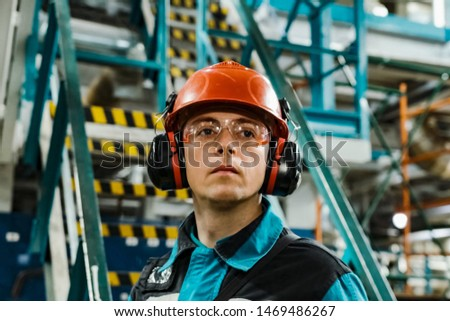 Tobolsk, Russia - June 19, 2019: A worker of an oil refinery in overalls and a helmet inspects equipment. #1469486267