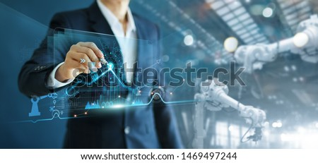 Manager engineer analyzing and control automation robot arms machine on software modern virtual interface data real time  in intelligent factory industrial and digital manufacturing operation.  #1469497244
