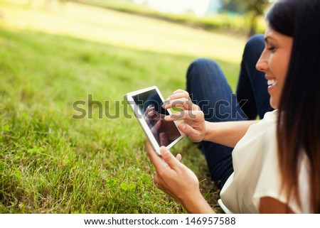 Happy woman using tablet outdoor laying on grass #146957588
