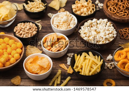 All classic potato snacks with peanuts, popcorn and onion rings and salted pretzels in bowl plates on wood. Twirls with sticks and potato chips and crisps with nachos and cheese balls. Top view Royalty-Free Stock Photo #1469578547