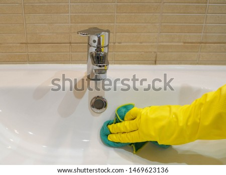 Woman in yellow rubber gloves cleaning a white water sink. Housewife holding a green rag. Modern bathroom. Cleaning company services. Housemaid washes the apartment. #1469623136
