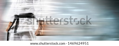 Guy poses in white kimono with black belt on motion background. Blurred effect. Sports banner  #1469624951