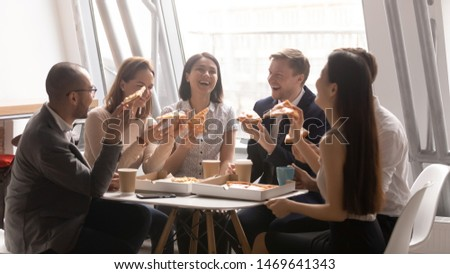 Overjoyed diverse multiethnic colleagues have fun eating pizza during lunch break in office, happy diverse coworkers laugh enjoy tasty delicious Italian fast food snack or dinner chatting and smiling #1469641343