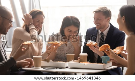 Excited diverse multiethnic colleagues have fun laughing eating delicious pizza together at lunch break in office, happy multiracial coworkers smile chatting enjoy Italian fast food snack at workplace #1469641346