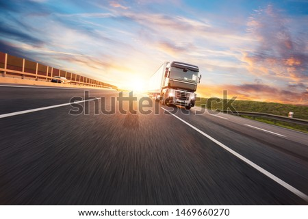 European truck vehicle on motorway with dramatic sunset light. Cargo transportation and supply theme. #1469660270