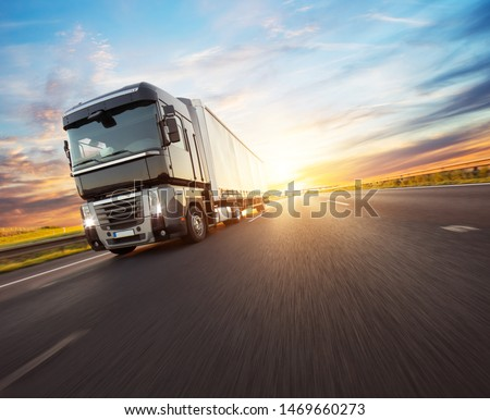 European truck vehicle on motorway with dramatic sunset light. Cargo transportation and supply theme. #1469660273