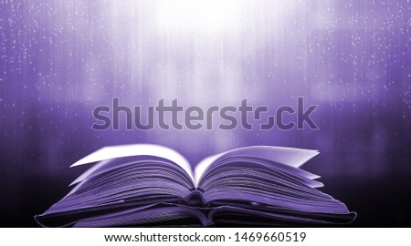 Imagine a picture book of an ancient book opened on a wooden table with a sparkling golden background. With magical power, magic, lightning around a glowing glowing book In the room of darkness #1469660519