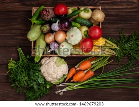 A bunch of ripe natural vegetables. Raw ripe vegetables in a wooden box. The concept of healthy and vegetarian food. Rich harvest on an agricultural farm. Raw vegetables on wooden background. #1469679203