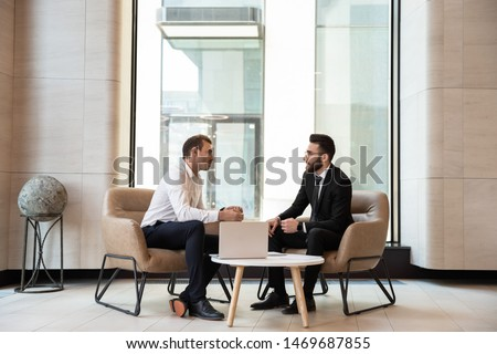 Businessmen discussing deal, sharing startup ideas, business partners negotiations or job interview in modern office with panoramic windows, colleagues talking, working on project together #1469687855