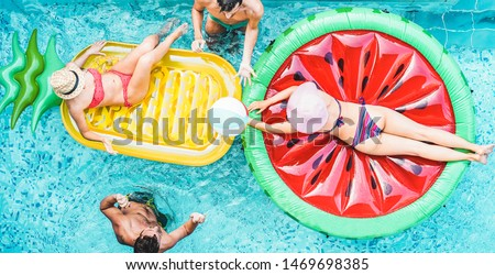Happy friends playing with air lilo ball inside swimming pool - Young people having fun on summer vacation - Travel, holidays, youth lifestyle, friendship and tropical concept #1469698385