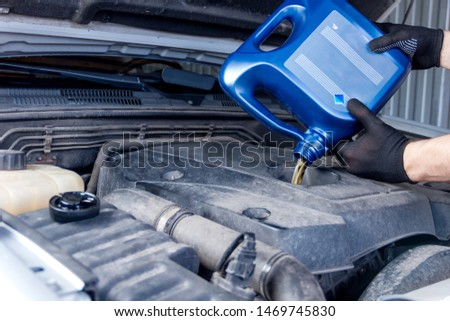 Mechanic is repairing, conducting diagnostics of car at service station. Repairer is holding blue canister and filling fueling engine oil in motor. Vehicle in workshop auto repair shop. #1469745830