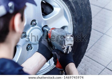 Back view of mechanic is repairing car at service station. Closeup repairman is removing wheel by electric wrench, tyre mounting equipment at workshop auto repair shop. Tire fitting concept. #1469745974