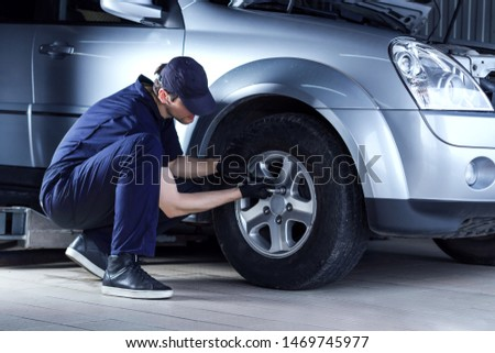 Mechanic man in blue jumpsuit is repairing car at service station garage. Repairman is unscrewing nuts on disk with wrench to remove wheel at workshop auto repair shop.Tire fitting concept. #1469745977