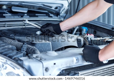 Closeup repairman hands are holding metal wrenches. Open hood with automobile motor on background. Repairer is repairing car at service station garage. Tool for mechanic at auto repair shop. #1469746016