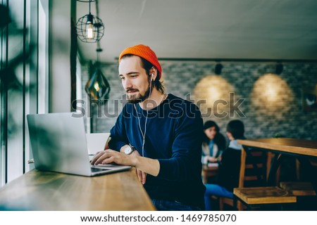 Caucasian male resting in coffee shop listening favorite music in headphones and chatting in social networks, skilled freelancer enjoying remote job typing publication for web blog on laptop #1469785070