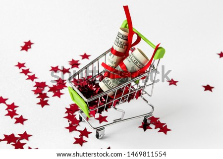 The dollar bill was folded and tied with a red satin ribbon in the shopping trolley. Isolated on white with red stars. Idea: sale of Christmas goods, discounts, purchases, purchases. #1469811554