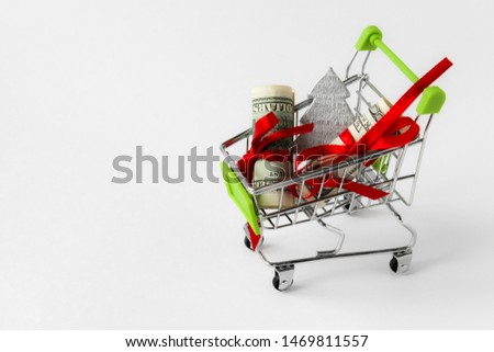 The dollar bill was folded and tied with a red satin ribbon in the shopping trolley. Isolated on white with red stars. Idea: sale of Christmas goods, discounts, purchases, purchases #1469811557