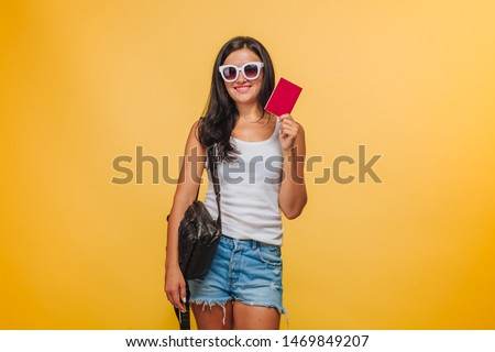 Girl tourist on a yellow background with a backpack and a passport #1469849207