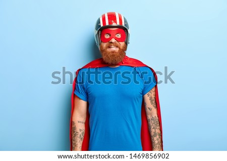 Glad bearded man with funny outlook, comes on costume party, being superhero character, wears helmet, mask and red cloak, has fun with friends, poses against blue background. Save world concept Royalty-Free Stock Photo #1469856902