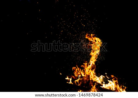Burning woods with firesparks, flame and smoke. Strange weird odd elemental fiery figures on black background. Coal and ash. Abstract shapes at night. Bonfire outdoor on nature. Strenght of element #1469878424