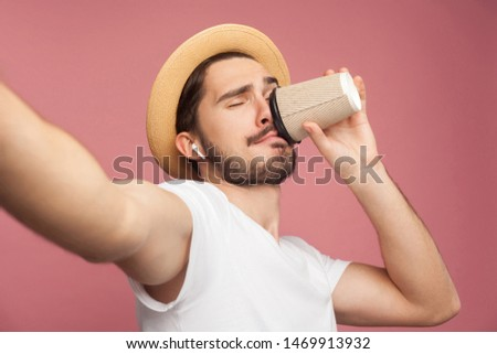 Close up portrait of fashion handsome bearded young hipster blogger in white shirt and casual hat posing and making selfie on phone, tasting coffee. Indoor,isolated, studio shot, pink background