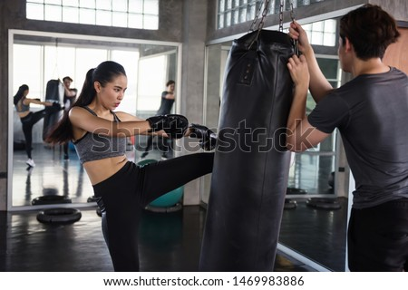 Asian Female boxer kick punching bag held by personal trainer at fitness gym. Athletic girl train Thai boxing punch and kick with coach for bodybuilding and healthy lifestyle concept. #1469983886