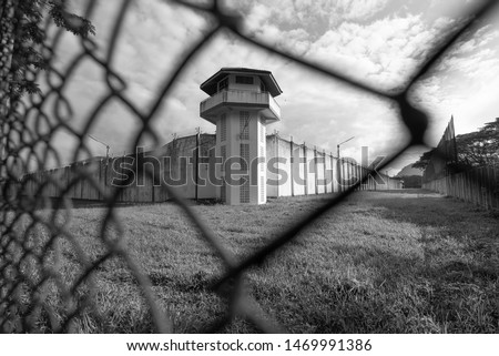Prison watchtower protected by wire of prison fence.White prison wall and guard tower with coiled barbed wire.Criminal justice imprisonment concept #1469991386