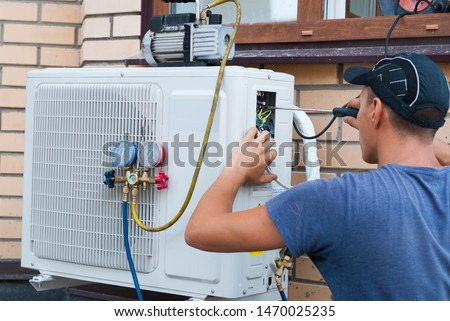 the worker installs the outdoor unit of the air conditioner on the wall of the house Royalty-Free Stock Photo #1470025235