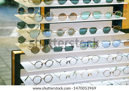 Stand with sunglasses. Sale the city market or in the store sunglasses. Trendy sunglasses, Summer eyeglasses, fashion collection, Different sunglasses on a stand.                                #1470053969
