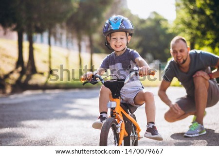 Father teaching his little son to ride a bicycle Royalty-Free Stock Photo #1470079667