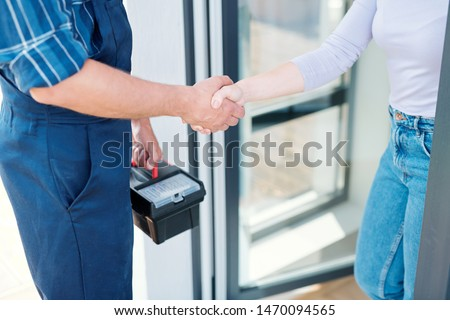 Young woman and technician saying goodbye while shaking hands after repair work Royalty-Free Stock Photo #1470094565