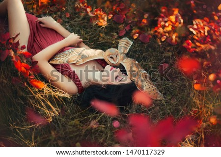 bright photo in burgundy shades, girl in dark dress color of Marsala, lady with dark hair lies on grass, fallen red and yellow leaves, barn owl spread its wings on sleeping fairy and protects sleep