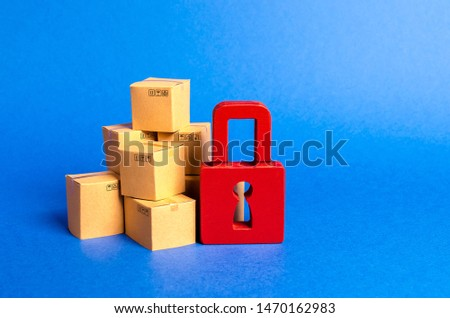A stack of cardboard boxes and a red padlock. concept of insurance purchases. Consumer rights Protection. cargo arrest customs clearance. ban on the import. Providing warranty on purchased products. #1470162983