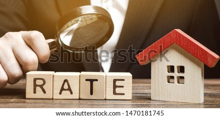 Wooden blocks with the word Rate, house and a magnifying glass in the hand of a man. The concept of studying interest rates on mortgages. Real estate and property. Loan and mortgage. Buying apartments #1470181745