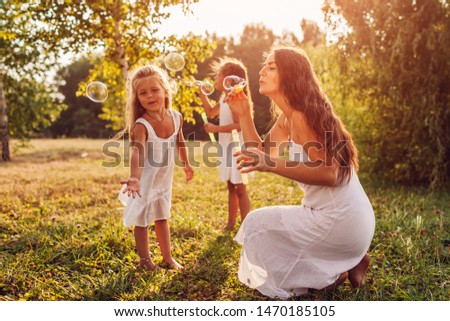 Mother helps daughters to blow bubbles in summer park. Kids having fun playing and catching bubbles outdoors #1470185105