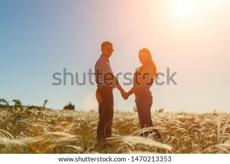 silhouette of two lovers at sunset in the field. #1470213353