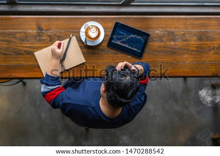 Asian business analyst watching stock trading graph on tablet #1470288542