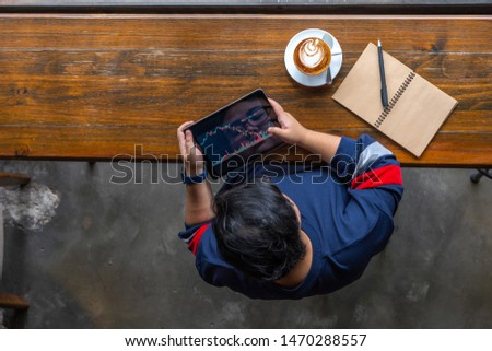 Young Asian investor tracking stock market trading graph on tablet #1470288557