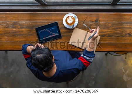 Young freelancer grabbing head while watching candlestick chart on tablet #1470288569