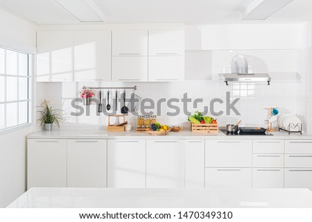 Modern white kitchen with counter and white details, minimalist interior with sunlight in daytime. Full set of kitchen equipment, pan, pot, electric hob, flipper, vegetable, fruit. #1470349310