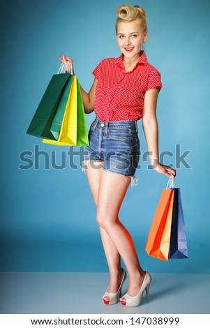 Retro style. Full length young woman in red dotted shirt and shorts with colourful shopping bags isolated on blue background #147038999