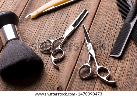 Barber tool on a wooden table. Scissors, comb for hair and a razor close-up. Hairdressing tool kit. Scissors and other tool barber. Barber set. #1470390473