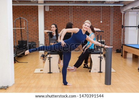 a pregnant woman in a blue tracksuit performs an exercise, women in the gym, women do Pilates, women do the simulator, women do Pilates, Pilates, fitness, #1470391544