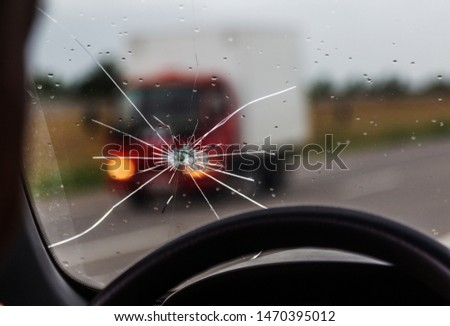 Broken windshield of a car. A web of radial splits, cracks on the triplex windshield. Broken car windshield, damaged glass with traces of oncoming stone on road or from bullet trace in car glass #1470395012