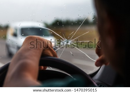 Broken windshield of a car. A web of radial splits, cracks on the triplex windshield. Broken car windshield, damaged glass with traces of oncoming stone on road or from bullet trace in car glass #1470395015