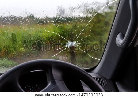 Broken windshield of a car. A web of radial splits, cracks on the triplex windshield. Broken car windshield, damaged glass with traces of oncoming stone on road or from bullet trace in car glass #1470395033