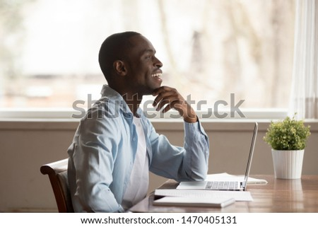 Happy young african american guy sitting at table with computer, distracted from work or studying, looking away, dreaming, visualizing future, weekend or vacation time, lost in positive thoughts. #1470405131