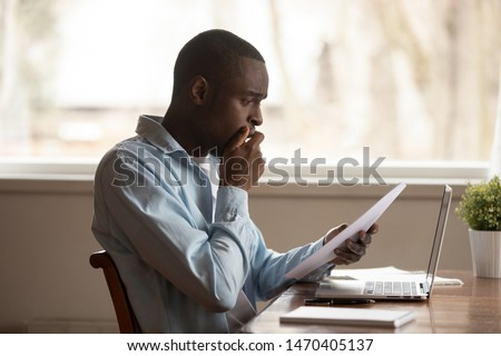 Upset unhappy young african american guy sitting at table, holding paper document, received bad news, dismissal notice, big debt notification or utility bill, financial problems, eviction notice. #1470405137