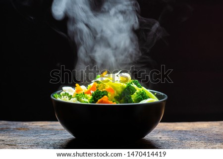 The steam from the vegetables carrot broccoli Cauliflower in a black bowl , a steaming. Boiled hot Healthy food on table on black background,hot food and healthy meal concept #1470414419